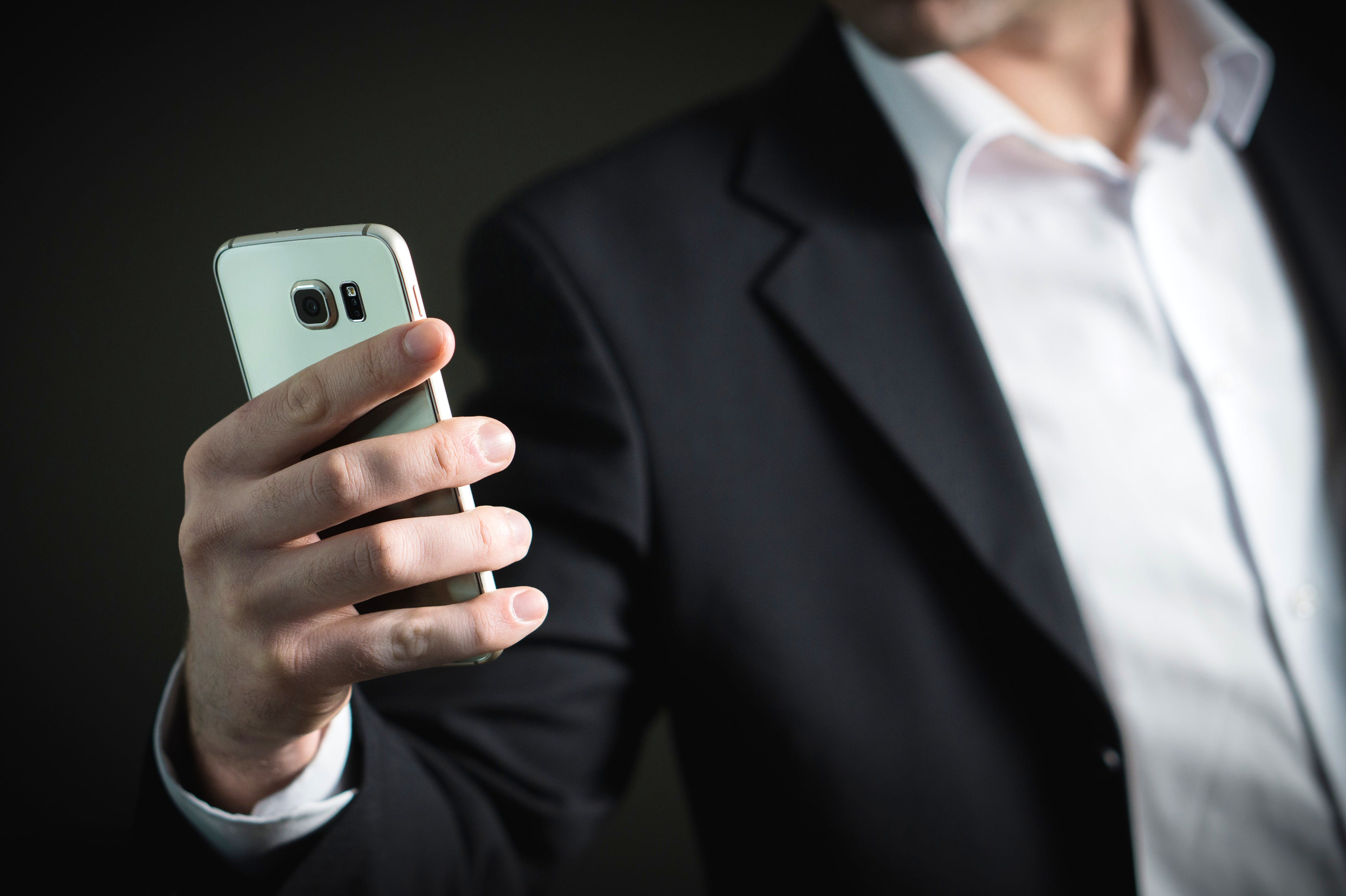 Mobile phone,Gadget,Suit,Smartphone,Formal wear,Finger,Communication Device,Technology,Electronic device,Hand