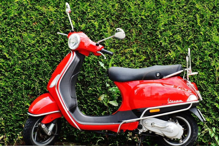 Vehicle,Motor vehicle,Red,Scooter,Car,Moped,Motorcycle,Grass,Automotive design,Plant