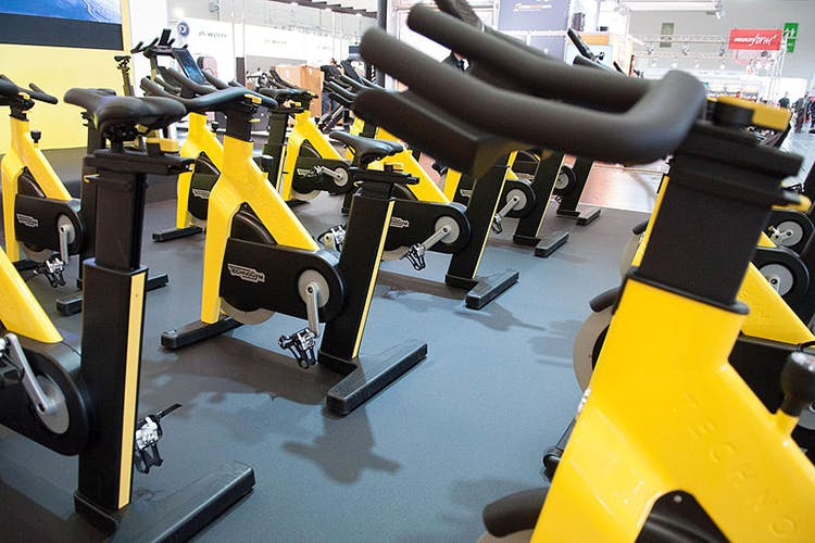 Gym,Yellow,Room,Indoor cycling,Sport venue,Physical fitness,Exercise equipment,Vehicle,Exercise,Exercise machine